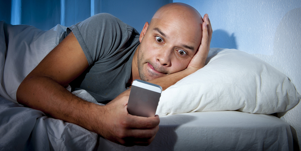 man-looking-at-smartphone-in-bed-night