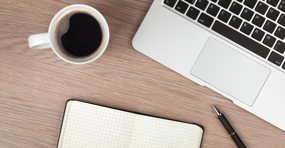 Notepad, laptop and coffee cup